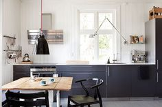Simple-Kitchen-Decoration-with-Swing-Arm-Wall-Lamp-Black-Cabinets-and-Rustic-Dining-Table.jpg (600×400)