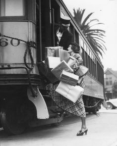A shopper during Downtown Dollar Days in Los Angeles needs help getting on the streetcar with all her purchases, c. 1933. S)