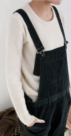cream sweater under black overalls