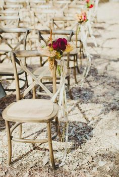 Paper flowers and ribbon on ceremony chairs