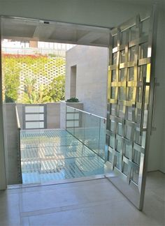 Custom basket weave stainless steel and glass door with the entry glass bridge that spans a tiled fountain below  -Andrew Williams and Associates, www.awagc.com