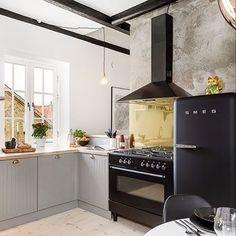Får man bjuda på lite köksinspo?  Ljust pigmenterat trägolv. Möter grå köksluckor med bänkskiva i trä. Ett fönster utan gardiner. Spotlights som ringlar ned från mörkt målade träbjälkar. Trä möter fondvägg av betong. Som möter stänkskydd i mässing. Spisen och kylen från Smeg ger köket karaktär och personlighet tillsammans med de olika materialen. Vackert!  Kvällens inspiration kommer från @erikolssonskane