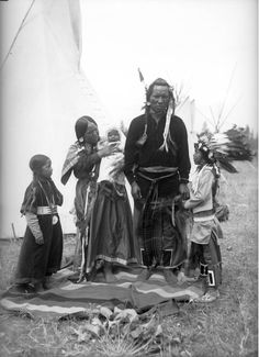Scoonay, a Native American man on the Flathead Indian Reservation in western Montana, stands with his family in front of a teepee on the reservation - Boos - 1905/1907