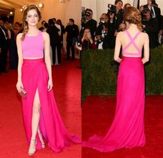 "Emma Stone scores yet another hit in this Thakoon ensemble. The pink crop top features a crisscross back, while the two-toned magenta wrap skirt offers a tantalizing glimpse of midriff & thigh. The eminently likable & lovely actress finishes off her cheerful look with a ""Frozen""-style side braid"