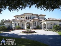 The Audrey Front Exterior by Tampa Custom Home Builder Alvarez Homes - (813) 701-3299 Beautiful roof and use of arches and columns! http://www.alvarezhomes.com/tampa-home-builders-portfolio-of-homes/the-audrey
