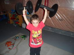 Fake weights made out of spools and painted black, kids loved this.  Superhero's have to be strong.