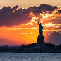 Sunset behind the Statue of Liberty by @nyclovesnyc #newyork #nyc