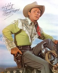 """A 35-year-old Roy Rogers, sporting an early appearance of his ubiquitous fringe cowboy shirt, is definitely prepared to face imminent danger while sitting atop Trigger, spring 1947: Note the authentic """"Happy Trails"""" autograph: Photo by Roman Freulich"""