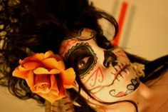 Day of the Dead face painting involves symbolism of both skulls and flowers.