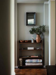 hall way with bookshelf with terracotta bowls and welsh blankets