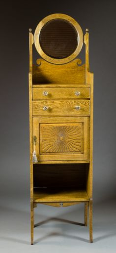 """LATE VICTORIAN OAK SHAVING STAND, American, c. 1900, a cabinet style stand with round tilt mirror over a 2-drawer/single-door cabinet with open shelf below, the four legs integral to the sides, 63""""H x 17""""W x 13""""D."""