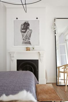 Bedroom with a fireplace mantel, unique art and a large standing mirror