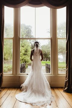Bride in white wedding dress framed by large bay window. Taken by Dublin-based professional wedding photographer Olga Hogan. Get in touch for your own pictures.