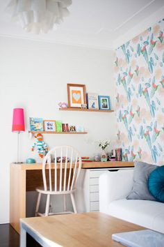 love the shelves above the desk, and the one wall that is papered. also, that blue pillow on the couch makes me happy!