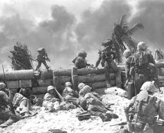 Betio Island, Tarawa Atoll, Nov. 20, 1943. Landing under fire, U.S. Marines of the 2nd Marine Division take cover behind the seawall while others climb over the top.
