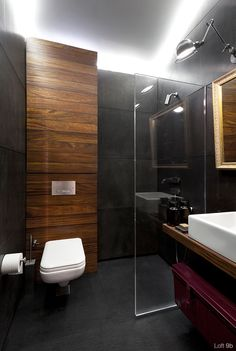 black concrete panel walls with traditional touches-light, mirror, countertop and metal trunk below, clubby colour wood behind loo