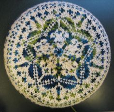 Hand knit. Fair Isle Tam. Two colors with one of the colors being variegated. Worsted weight. Called Flower Love.