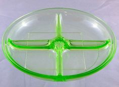Candy Nut Dish Depression Vaseline Green Glass Art Deco 4 Part    Nearly a century ago, dozens of glass companies made similar round flat candy dishes, but this one upon close inspection stands out from all the others.     First, the divided four part is unusual.  Looking at the center hub, there is a stepped diamond pattern that just catches the eye.      Art deco look or feel?  I think yes.     Not in perfect condition but near perfect.  The divided candy dish is made from uranium vaseline…