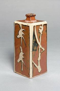 Hamada Shoji a moulded square Bottle with wax-resist designs stoneware, persimmon glaze with wax-resist edges, each face with a different flower stem or bamboo design Height 9 1/4in. (23.2cm)