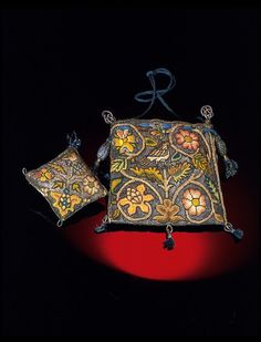 Physical description Purse with matching pincushion, embroidered with silver and silver-gilt thread and coloured silk, in tent and braid stitches. Drawstring of blue silk braid. A design of birds amongst floral sprays Place of Origin England, Great Britain (made) Date 1600-1650 (made)