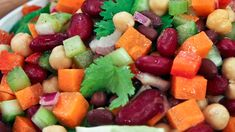 A colourful salad filled with beans, chickpeas, cilantro, red peppers, carrots, red onions, and celery.