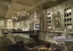 IVORY KITCHEN  Architectural kitchen in ivory with British antique grey glaze and black oak veneer with enhanced frieze and mantel.  Integrated tv, barrel-backed alcoves with statuettes, bevelled glass-fronted cabinetry with Clive Christian Monogram wallpaper and Empire high back stools.
