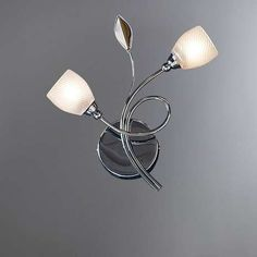 Our wall light is designed with a swirling chrome arm that holds two tulip-shaped glass light shades and is finished with simple leaf detailing. Wall Lights, Ceiling Lights, Wall Mounted Light, Floral Wall, Home Lighting, Home Furnishings, Sconces, Table Lamp, Home Decor