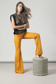 Em malha suede super elástica e leve, a calça Sevilha mostarda une conforto e estilo. Com o cós largo, o fechamento se dá através de zíper e botões forrados no próprio tecido. Nas pernas, os recortes são realçados por pespontos duplos.   Ateliê de Calças