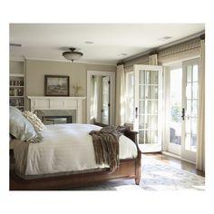 Wood bed tan walls fireplace French doors ivory drapes bamboo roman shades