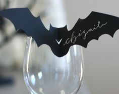 Get a calligrapher to hand-write the names of your guests on bat-shaped place cards. Photo via Pinterest .