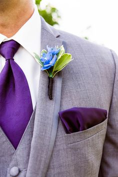 Pair a light gray tuxedo with a purple paisley tie, delphinium boutonniere and a pocket square for a bold groom's style! {@amandamacdo0496}