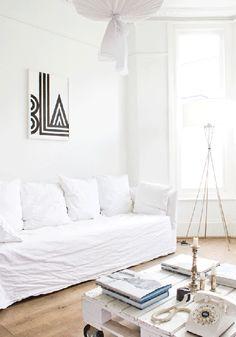 retapizado de sofá en lino blanco, rústico y preciso. Palet pintado de blanco y cuadro simple (ByN). En este caso, la vivienda aporta toda su sobriedad y categoría.