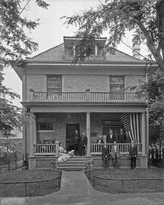 Men and women sitting on and in front of a porch in 1912. Note greek columns and simple porch rail