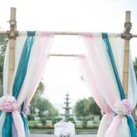 Natural Bamboo Arbor, Peacock, blush and white fabrics accent this natural bamboo Wedding arbor.