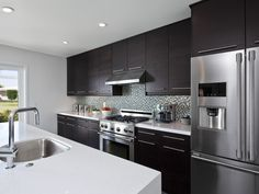 The focal point of the kitchen was the oversized island. The counter tops were blizzard white Ceasarstone highlighted with a 3/8″ glass and stone mosaic tile backsplash reminiscent of a colorful mid-century tile. With the use of out-of-the-box cabinetry and careful attention given to appliance and other finish selection, the end result was a functional open plan kitchen with a spectacular presence completed at a fraction of the cost of a comparable custom kitchen.