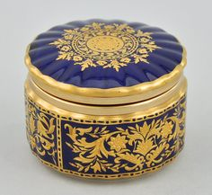 Sevres style porcelain tabatiere box with hinged lid of gadrooned porcelain and gilt metal rims decorated with raised floral gilt design on cobalt blue background, prob. France