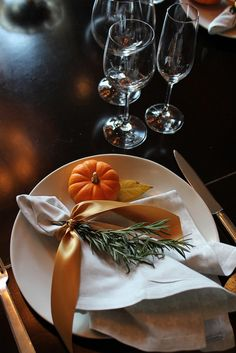 Tie a pretty warm hued ribbon, or kitchen twine, or raffia into a bow, around your napkin. Tuck fresh herbs, like fluffy, scented Rosemary into the bow for a savory textural touch.