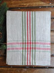 Bright red and green lines dash across this festive woven linen tea towel.  Poshchicago.com