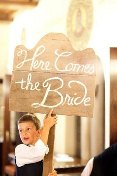 great idea... boy with a sign to introduce the bride