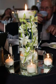 Love the floating candle with submerged orchid as an idea for one of the centerpieces