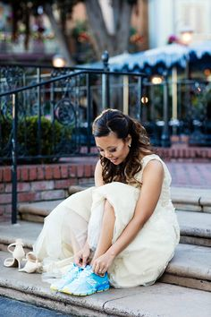Disneyland bride laces up her runDisney Cinderella New Balance's during her portrait session in the park.