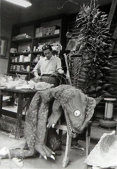 Kaiju suit builder Ryosaku Takayama at work. Kaiju Bemular is suspended at right, Ultra Q kaiju Peter waits on the work bench. Peter would be revised to become Gesura for the Ultraman series.