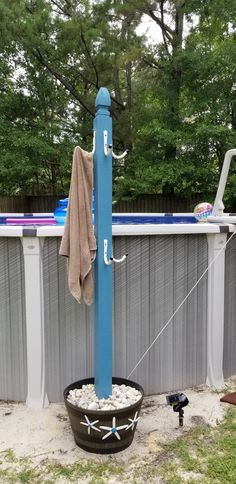 Pool Towel Stand. I made this one for my Dad. I used a 6 1/2 foot treated 4x4 and added a post cap to the top. I used garage hooks, painted them a cream color to match the starfish. Placed the 4x4 in a flower pot with a few inches of quick-create to keep it centered and upright.  Then put sand on top of quick-crete and added rocks of top.