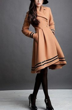 Beautiful coat (or maybe coatdress). The color is pleasing and the shape and trims are in harrmony. Artistic fashion.