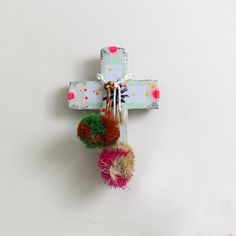 • Mixed medium decorative cross • Approximately 14x17cm • Not suitable for outdoor use • All pieces are unique - paint splashes and pom pom colour will vary • Designed by Jai Vasicek and handmade in Byron Bay, Australia