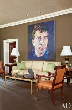 Designer Thomas Jayne convinced the owners of this Philadelphia home to line the living room walls in a chocolate-brown Holland & Sherry cotton, providing a distinctive backdrop for the large Chuck Close portrait, Bill, and other artworks  | archdigest.com