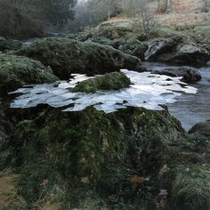 Thin ice formed overnight lifted from river pools frozen around a rock Scaur Water, Dumfriesshire, December 1991