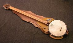 """Another gorgeous piece by Dismal Axe, this time a crazy hybrid banjo/dulcimer, or """"banjimer. Even better, she put a couple of pickups in there and wired them as a humbucker. Cigar Box Guitar, Dulcimer Music, Mountain Dulcimer, Custom Electric Guitars, Musical Toys, Guitar Art, Banjo, Skyrim, Musical Instruments"""