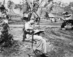 The Campaign in New Guinea, December 1942 - 1943: An artillery observer prepares to be hoisted to the top of a tree in a special chair to observe a bombardment of Japanese positions.