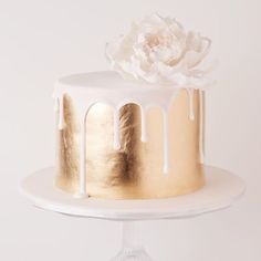 Gold cake with white flower www.thebohemianwe... Follow us on Instagram & Facebook @thebohemianwedding